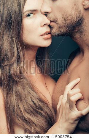 young sexy couple of woman or girl with pretty face and long hair embrace handsome muscular unshaven man with bare chest or breast on body