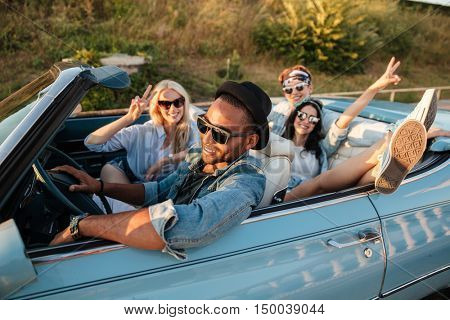 Group of smiling young friends driving car and showing peace sign in summer
