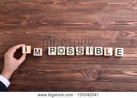 Human hand turning word impossible into possible