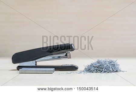 Closeup black stapler with blurred pile of used staples and new staples office equipment on blurred wood desk and wall in office room textured background under window light
