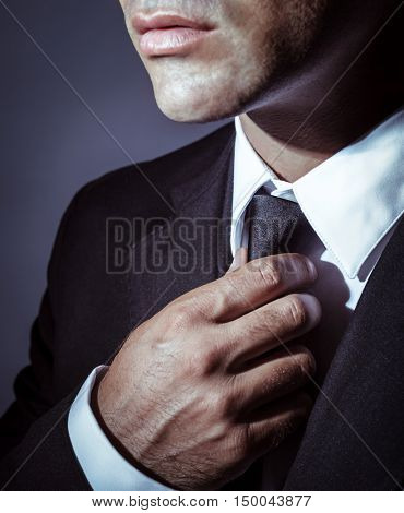 Closeup photo of a serious businessman wearing stylish black suit and tie over dark background, face part, men's wear fashion concept