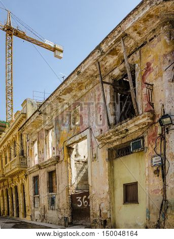 HAVANA - CUBA JUNE 19, 2016: A modern crane rises over one of the many deteriorating blocks of crumbling buildings on Calle Inquisidor as rebuilding continues in the La Habana Vieja neighborhood