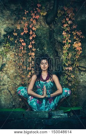 young woman in meditate yoga position outdoor  in front cliff with autumn leaves