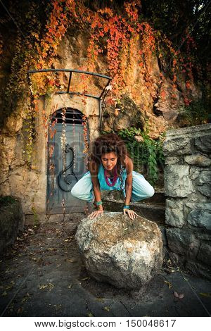 young woman practice balance on rock outdoor in front old wall and cliff autumn day