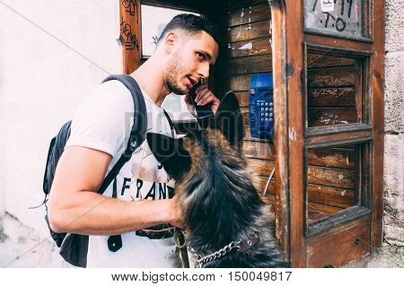 man and a dog in a phone booth, posing at the camera