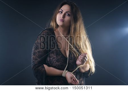 Young naked beautiful caucasian plus size model xxl woman in black peignoir on smoky studio background beauty female nude body with big breast