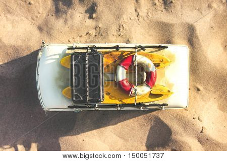Toy minivan with bag and surfboards on sand beach top view