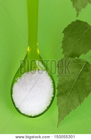 Xylitol birch sugar on plastic spoon with birch leaves over green. White granulated sugar alcohol, substitute used as sweetener that taste like table sugar, extracted from the wood of birch trees.