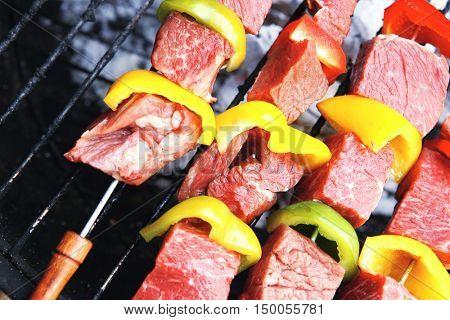 fresh raw beef shish kebab with pepper chunk on black big grill bbq