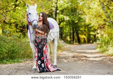 Young woman walks with white horse by alley in park.