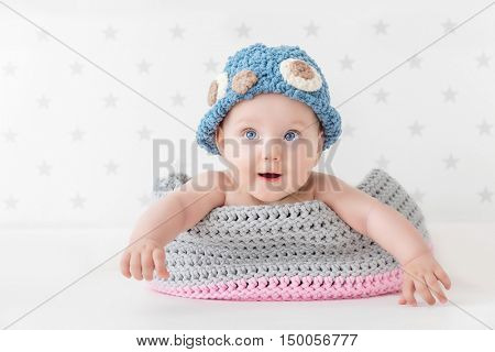 Cute baby lying happy in a woollen basket and wearing a funny beanie. Child room wallpaper in grey stars.