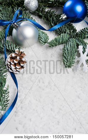 Close up of silver and blue christmas balls on snowy fir branch. Xmas decoration with pine cone and snowflake on white snow. Christmas tree and blue ribbon with copy space.