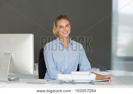 Young beautiful business woman with computer in office. Portrait of beautiful receptionist working on computer. Portrait of smiling businesswoman sitting at help desk and looking at camera.