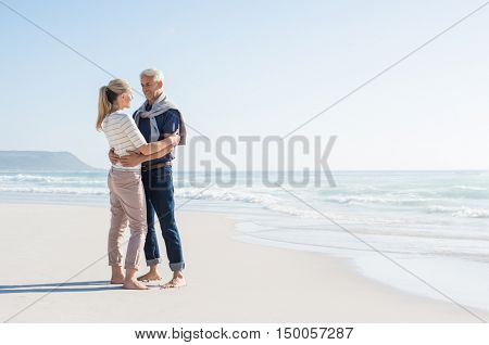 Cheerful mature couple embracing on the beach with copy space on right. Happy senior couple looking at each other at seaside. Romantic retired couple on summer vacation at sea.