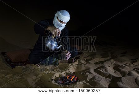 Man in traditional Tuareg outfit making tea in a desert at night