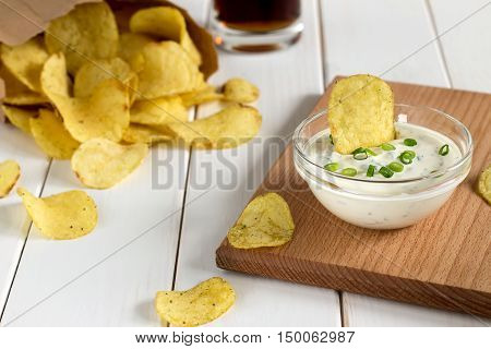 Potato Chips In A Paper Bag And Dipping Sauce On A Wooden Table.