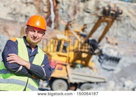 worker in front of heavy excavator and dumper truck
