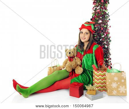 A pretty teen elf relaxed by a sparkly tree and surrounded by Christmas gifts.  On a white background.