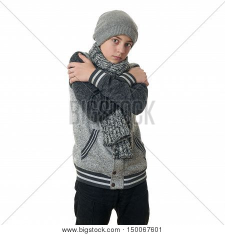 Cute teenager boy in gray sweater, hat and scarf trying get warmer with crossed arms over white isolated background, half body