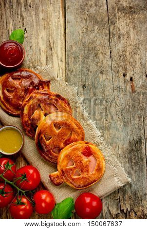Halloween pizza recipe idea - homemade calzone shaped pumpkin with ham cherry tomatoes and basil. Italian cuisine rustic style top view blank space for text
