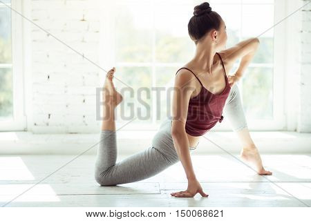 Physical exercise. Slender attractive dark haired girl doing her stretching exercises and looking through the window while having a dance class