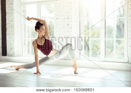 Grace and elegance. Attractive slender elegant woman holding her hand up and stretching while doing a physical exercise