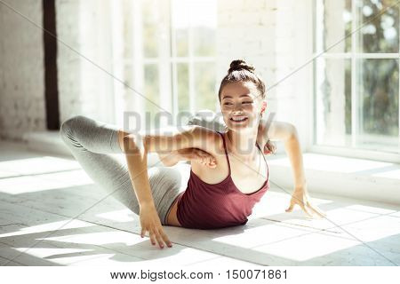 Enjoying a workout. Happy elated nice female dancer stretching her back and smiling while lying on the floor