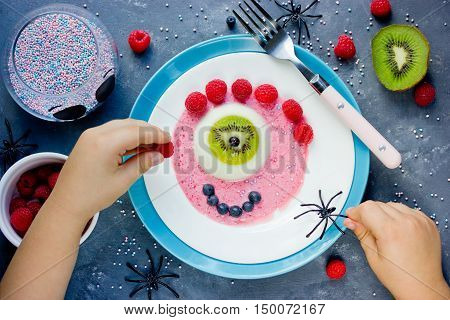 Halloween recipe one-eyed panna cotta with kiwi blueberry raspberry and sweet sauce. Creative idea for kids dessert on holiday party. Child hands holding cutlery baby eating concept top view