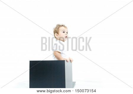 Portrait of cute baby sitting in a black wooden box on a white background