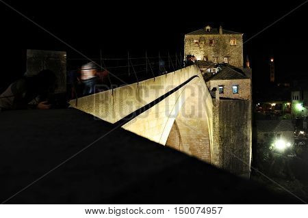 Tourists on the the old bridge of Mostar known as Stari Most at night