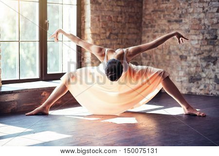 Involved in a process. Good looking professional female dancer bending down and moving her arms while having a workout