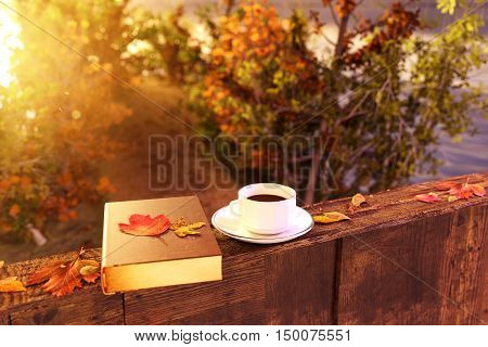 3d rendering of cup of coffee on wooden windowsill with leaves in front of footpath in beautiful autumn sunlight
