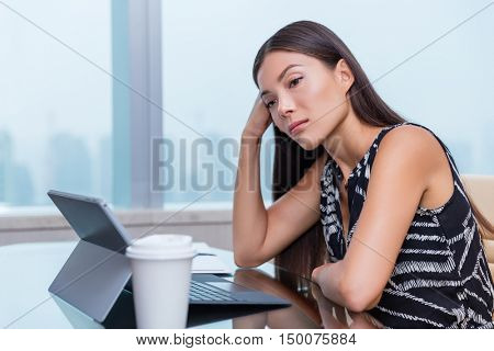 Bored or sad woman working at office job. Negative work concept. Tired businesswoman sitting at desk in front of laptop thinking about problems and showing dissatisfaction of career.