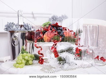 Glasses of champagne, a fruit bowl, a bucket of champagne on New Year's table,