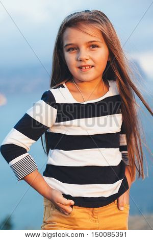 6-7 years old child wearing navy striped t-shirt posing over blue sea
