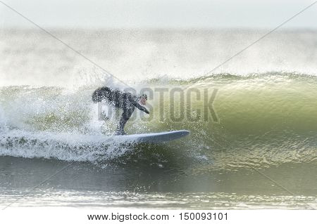 Little Compton Rhode Island USA - January 17 2016: Surfer tucked into small wave at Goosewing Beach