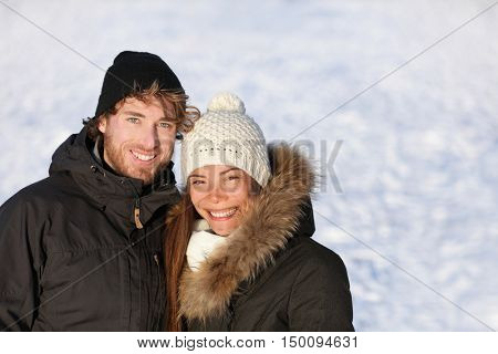 Happy winter interracial couple outdoors portrait. Cute young adults smiling in warm outerwear knit hat and down coats outside. Asian chinese woman, Caucasian man. White snow ice background texture.