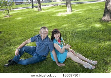 Man and woman relaxing on the green grass