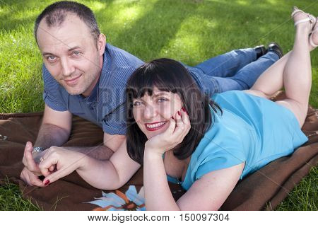 Middle-aged couple relaxing in the park on the grass