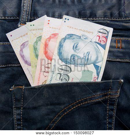 Singapore money bill in blue  jean pocket