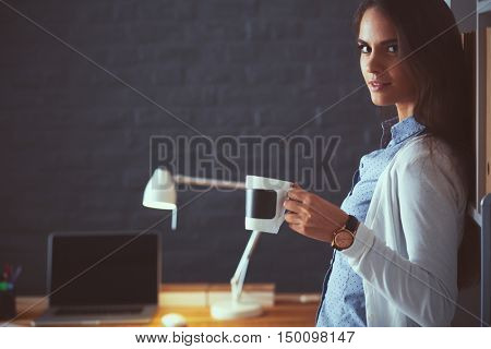 Young woman standing near desk with laptop holding cup of coffee