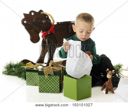 An adorable preschooler opening his gifts on Christmas Day.  On a white background.
