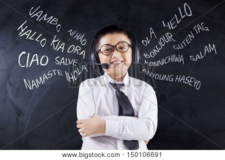 Language learning concept. Cute little boy learns multilingual while wearing headphones in the classroom