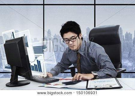 Young businessman working with calculator and virtual financial graph on the computer monitor shot in the office
