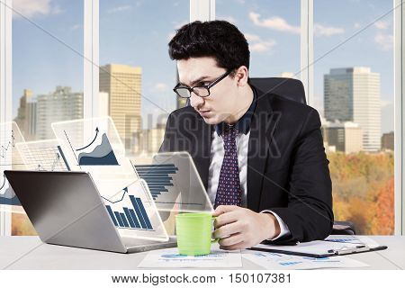 Photo of a Caucasian entrepreneur working with virtual financial statistics on the laptop and holding a cup of coffee in the office