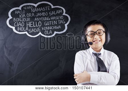 Language learning concept. Little boy standing in the classroom while wearing headphones and learn multilingual