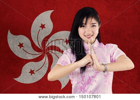 Image of beautiful young girl wearing cheongsam dress and congratulate Chinese new year with flag of Hong Kong