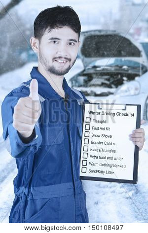 Male mechanic showing thumb up while holding clipboard with list of winter driving tips