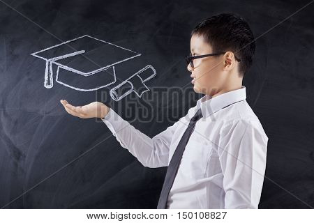 Photo of a little schoolboy standing in the class while holding a mortarboard icon on the chalkboard