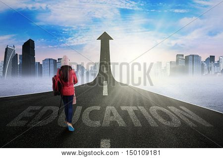 Young student wearing warm clothes and walking on the highway turning into upward arrow to gain higher education